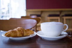 Hot coffee and fresh croissant on table Stock Photography