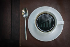 Hot coffee with graph reflex on top, business concept Stock Photos