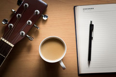 Hot coffee with guitar and notepad on table break time for think Stock Photo