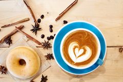 Hot coffee heart in blue cup and donut on wooden Royalty Free Stock Photo