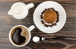 Hot coffee, jug milk and muffins on table. Hot coffee, jug milk and muffins in saucer on dark table. Top view Royalty Free Stock Images