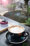 Hot coffee with latte art and cake with garden backyard in backg. Round, Lifestyle concept stock image