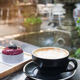 Hot coffee with latte art and cake with garden backyard in background, Lifestyle concept stock images