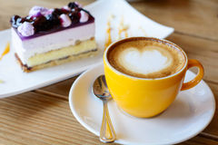 Hot coffee latte art and coffee foam with Blueberry Cake on wood. En table stock photography