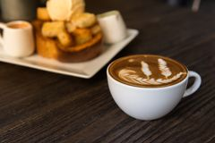 Hot coffee latte art cup. On wooden table stock image