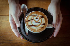 Hot Coffee with latte art. In female hands Stock Photography
