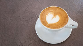 Hot coffee latte art heart shape foam on leather background Stock Photography