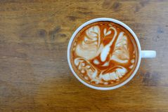 Hot coffee with latte art. In a white cup on a wooden table, top view, copy space royalty free stock image