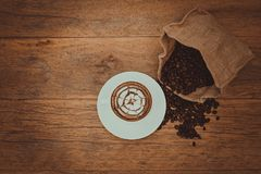 Hot coffee latte art with pattern on top by flat lay photography. Warm feeling coffee, vintage cup with light flare Royalty Free Stock Photo
