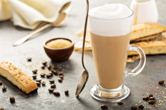 Hot coffee latte with biscotti cookies. Hot coffee latte with brown sugar and biscotti cookies in tall glass royalty free stock images