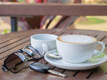 Hot coffee latte in a glass of white paste on a wooden table, With sunglasses and car keys Stock Photos