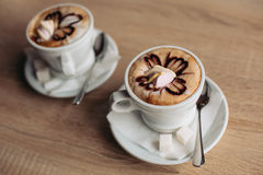 Hot coffee latte in white cup decorated, latte art. Cup of cappuccino with latte art on a plate and wooded table Royalty Free Stock Photos