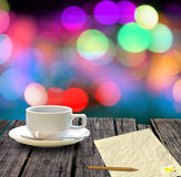 Hot coffee and letter paper on table with bokeh. Hot coffee and letter paper on wooden table with colorful bokeh background, Letter concept Stock Image