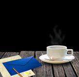 Hot coffee and letter on wooden table Royalty Free Stock Photography