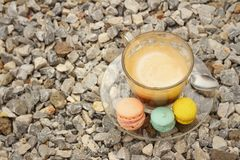 Hot coffee with macaron on the coasters. Royalty Free Stock Images