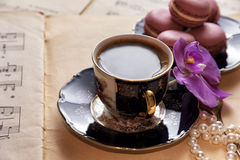 Hot coffee with macaroons, orchid and pearls. Hot coffee with macaroons, notes, orchid and pearlsn Stock Photos