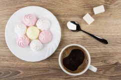 Hot coffee, meringues in plate, sugar and spoon on table Royalty Free Stock Image