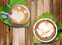 Hot coffee with milk foam art with leaves under mugs, on old wooden desk Royalty Free Stock Image