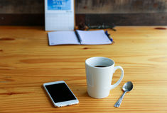 Hot coffee with mobile phone on the wood table Stock Images