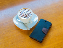 Hot coffee and mobile. White cup of hot coffee smartphone on wood table Stock Photography