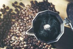 Hot coffee in moka pot with coffee bean. Top view royalty free stock image