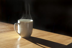 Hot Coffee Mug. A cup of hot coffee on a table in a white mug against a black background in a sunbeam Royalty Free Stock Photo