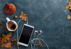 Hot coffee in mug and bun, mobile phone with headphones and autu Royalty Free Stock Photos