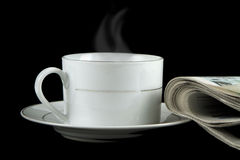 Hot coffee and newspaper on black background. Conceptual image Royalty Free Stock Image