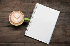 Hot coffee and notebook on wood table Stock Image