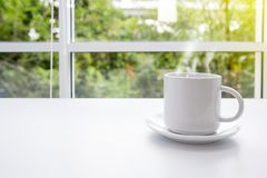 Hot coffee on old table with blur background. Coffee cup on the table in the morning. Background is a train in the capital. Thailand stock photos