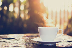 Hot coffee on old wood table with blur background of sunlight shining through the trees. Soft focus, vintage style color effect royalty free stock photography