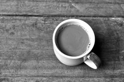 Hot coffee on old wooden plank in low key black and white style royalty free stock image