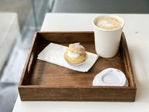 Hot coffee in paper cup and Choux Cream stock photos