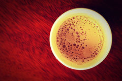 Hot coffee in paper cup seen from top, vintage style process Royalty Free Stock Images