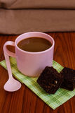Hot coffee in pink cup with brownie. And spoon on cloth Stock Photos