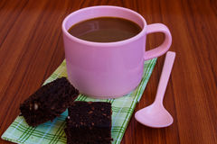 Hot coffee in pink cup with brownie. And spoon on cloth Stock Photography