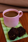 Hot coffee in pink cup with brownie. And spoon on cloth Stock Image