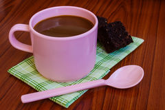 Hot coffee in pink cup with brownie. And spoon on cloth Royalty Free Stock Image