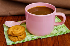 Hot coffee in pink cup. With cookies and spoon on cloth Royalty Free Stock Images