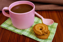 Hot coffee in pink cup. With cookies and spoon on cloth Royalty Free Stock Photo