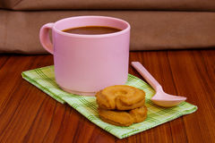 Hot coffee in pink cup. With cookies and spoon on cloth Stock Images