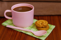 Hot coffee in pink cup. With cookies and spoon on cloth Royalty Free Stock Photography