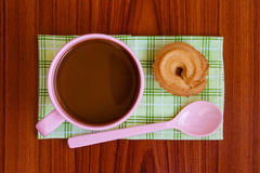 Hot coffee in pink cup. With cookies and spoon on cloth Stock Image