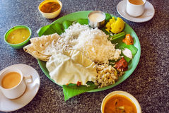 Hot coffee and plate with South Indian food thali with rice and spicy vegetables, on palm leaf in indian cafe. Royalty Free Stock Photo
