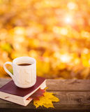 Hot coffee and red book with autumn leaves on wood background - seasonal relax concept.  Royalty Free Stock Image