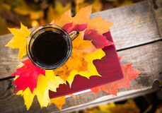 Hot coffee and red book with autumn leaves on wood background - seasonal relax concept.  Stock Photos