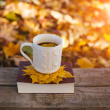 Hot coffee and red book with autumn leaves on wood background - seasonal relax concept.  Royalty Free Stock Photo