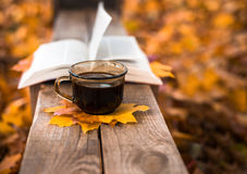 Hot coffee and red book with autumn leaves on wood background - seasonal relax concept.  Royalty Free Stock Images
