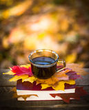 Hot coffee and red book with autumn leaves on wood background - seasonal relax concept.  Royalty Free Stock Photography