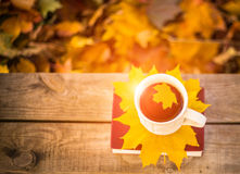 Hot coffee and red book with autumn leaves on wood. Seasonal relax concept with fallen leaves and hot drinks Stock Photos